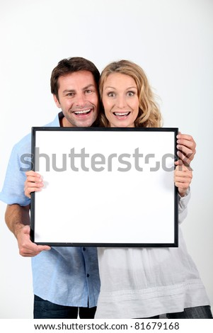 Excited couple with blank picture frame