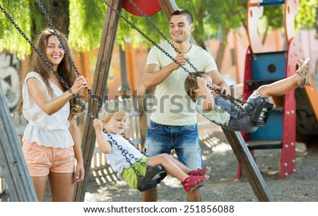 Excited daughters on swings with young parents. Focus on woman - stock photo