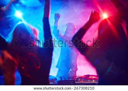 Excited deejay and dancing crowd enjoying disco party in nightclub - stock photo