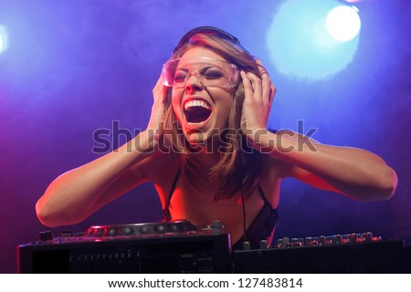 Excited DJ girl on decks on the party - stock photo