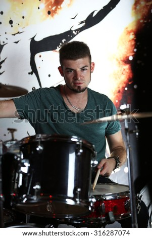 Excited drummer on bright background - stock photo