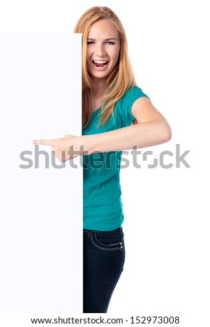 Excited enthusiastic woman laughing and pointing to a blank sign which she is holding alongside herself, isolated on white