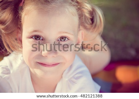 Excited face of pretty small girl in summer park