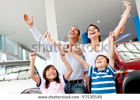 Excited family buying a car and celebrating with arms up - stock photo