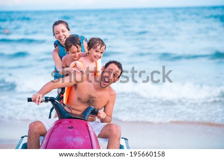 Excited family riding jet ski - stock photo