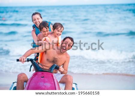 Excited family riding jet ski - stock photo