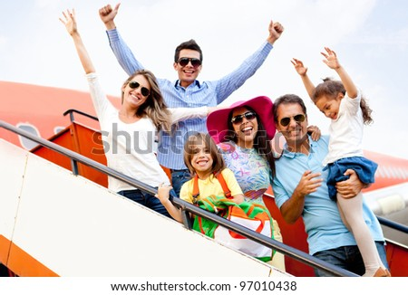 Excited family with arms up traveling by airplane - stock photo