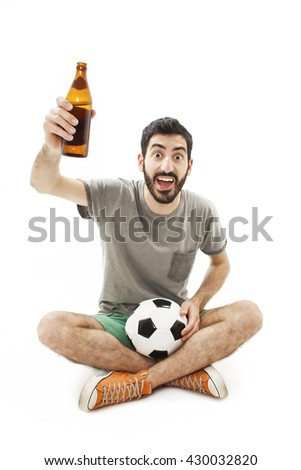 Excited fan holding a ball and beer, cheering. Sitting on floor. Isolated on white background - stock photo