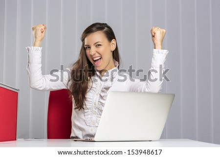 Excited female executive screaming and celebrating with raised clenched fists her business victory in front of laptop in the office.