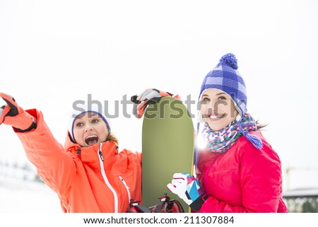 Excited female friends with snowboard outdoors - stock photo