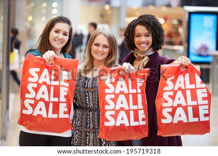 Excited Female Shoppers With Sale Bags In Mall - stock photo