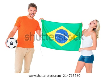 Excited football fan couple holding brazil flag on white background - stock photo