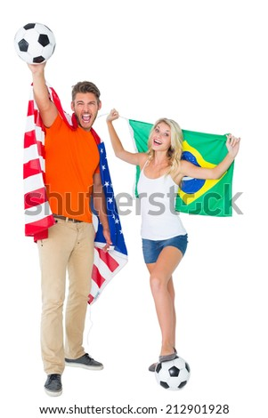 Excited football fan couple holding usa and brazils flag on white background - stock photo