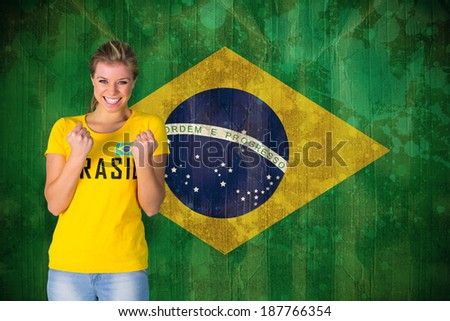 Excited football fan in brasil tshirt against brazil flag in grunge effect - stock photo