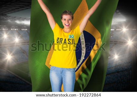 Excited football fan in brasil tshirt holding brasil flag against large football stadium with fans in blue - stock photo