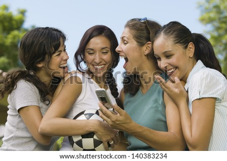 Excited four young women smiling and looking at mobile phone outdoors