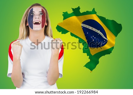 Excited france fan in face paint cheering against green brazil outline with flag - stock photo