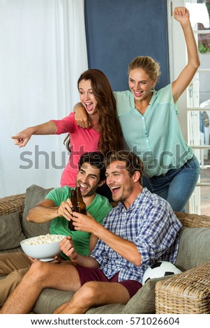 Excited friends having popcorn and beer watching football match at home