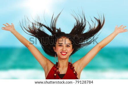 Excited girl at the beach throwing her arms in the air - stock photo