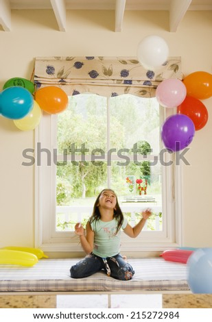 Excited girl (4-6) kneeling on window seat at home, looking up at party balloons attached to wall, smiling, front view - stock photo