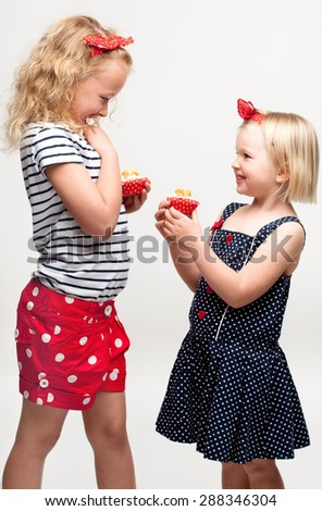 Excited Girls with delicious cupcakes - stock photo