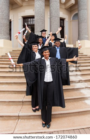excited graduates standing outside college building - stock photo