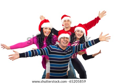 Excited group of friends wearing colorful clothes and Santa hats and standing with  hands in the air laughing isolated on white background