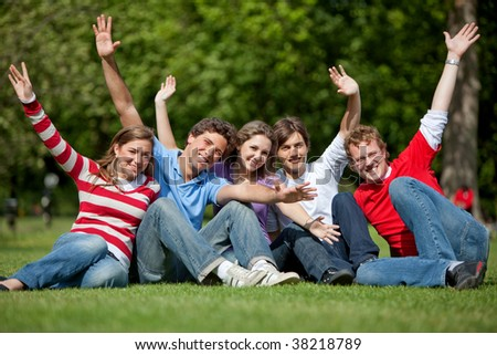 Excited group of friends with raised arms outdoors