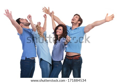 excited group of young casual people celebrating success and looking up with hands in the air - stock photo