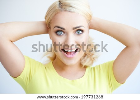 Excited happy attractive young woman holding her long blond hair back from her face with her hands looking at the camera with a surprised wide eyed expression - stock photo