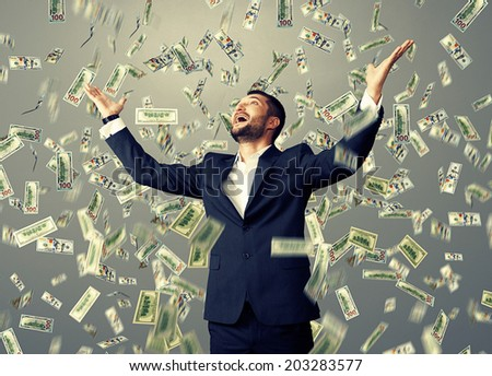 excited happy businessman standing under dollar's rain and looking up
