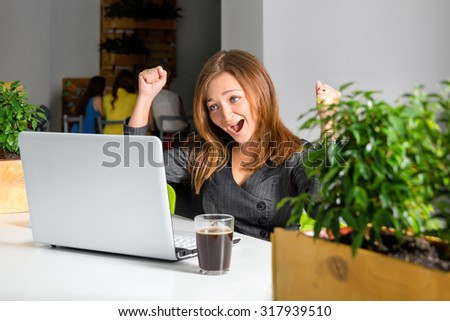 Excited happy businesswoman with raised arms sitting at the table with laptop celebrating her success. Green eco office concept - stock photo