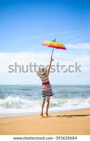 Excited happy female having fun on beach run and jump on sunny background outdoors