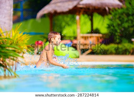 excited happy kid boy having fun in pool, summer vacation - stock photo
