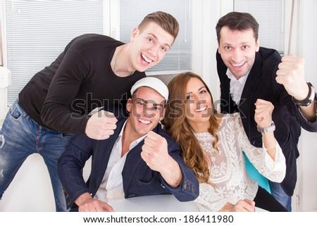 excited happy modern group of friends and colleagues showing sign of win and success with clenched fists