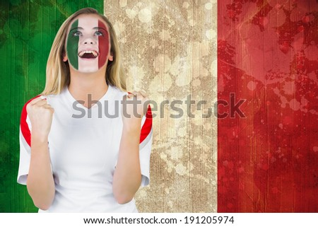 Excited italy fan in face paint cheering against italy flag in grunge effect - stock photo