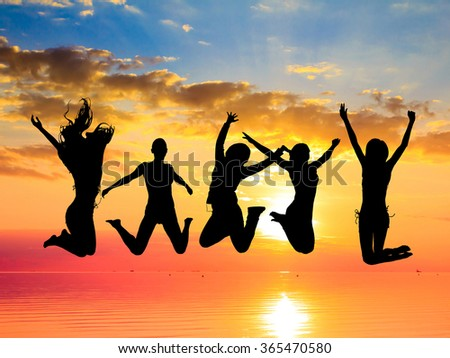 Excited Jumping over Sunset  - stock photo