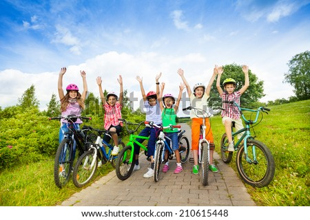 Excited kids in helmets on bikes with hands up - stock photo