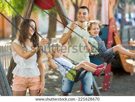 Excited kids on swings with young parents. Focus on woman - stock photo