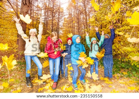 Excited kids play together with flying leaves