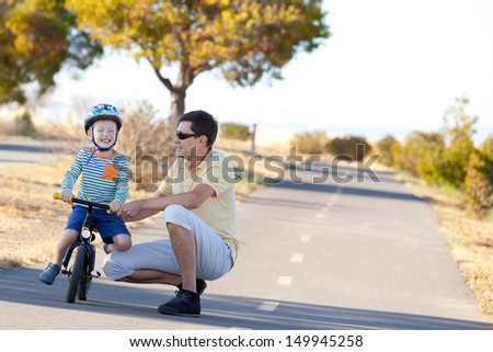 excited laughing boy at the balance bike and his father together walking and enjoying - stock photo