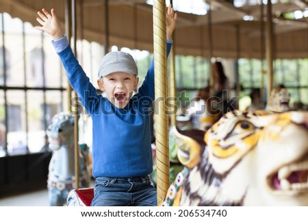 excited little boy enjoying his ride at carousel in amusement park - stock photo