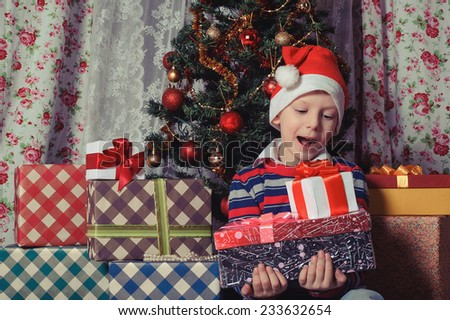 Excited little boy  in Santa red hat holding christmas presents in front of the fir tree - stock photo