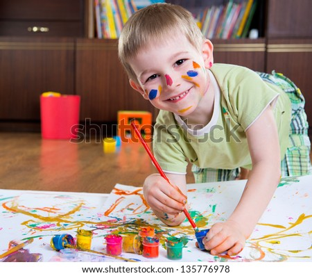 Excited little boy painting with colorful paints