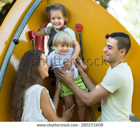 Excited little daughters climbing at playground ladder with young parents