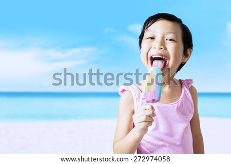 Excited little girl enjoying ice cream on the beach while wearing swimsuit - stock photo