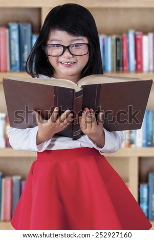 Excited little girl smiling at the camera while holding a textbook in the library - stock photo