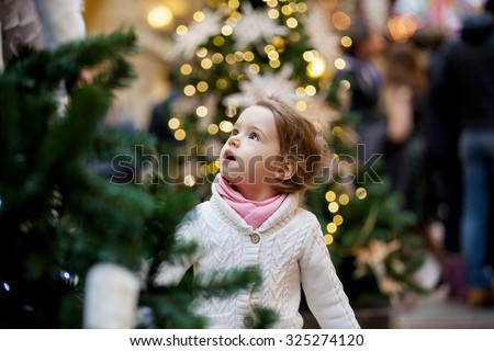 Excited little girl with open mouth looking at the beautifully decorated christmas trees with lights in the shopping mall - stock photo