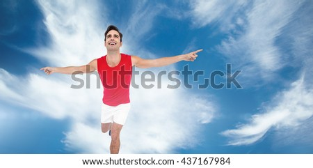 Excited male athlete with arms outstretched against blue sky with clouds