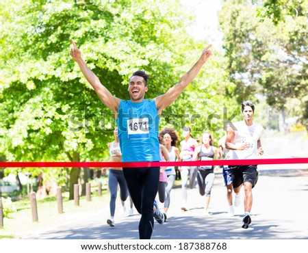 Excited male runner crossing the finshline of a marathon - stock photo